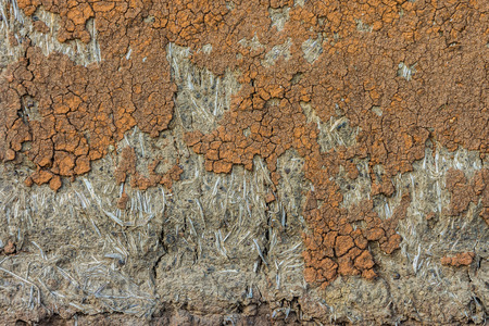 subsoil: Cracked wall of cob house for background and texture. It is a natural building material made from subsoil, water and some kind of fibrous organic material. Stock Photo
