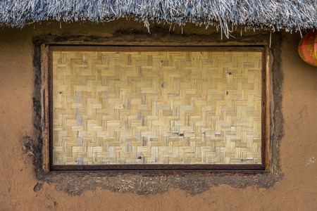 chaff: Bamboo wickerwork window of a vintage cob house in Northern Thailand