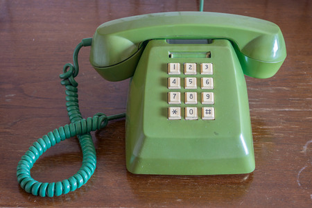fixed line: Old traditional landline telephone on wooden table Stock Photo