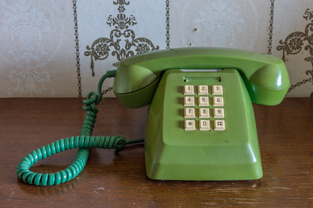 fixed line: Vintage traditional home telephone on wooden table Stock Photo