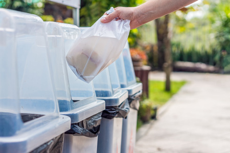 waste material: Hand throws away waste material into trash container Stock Photo