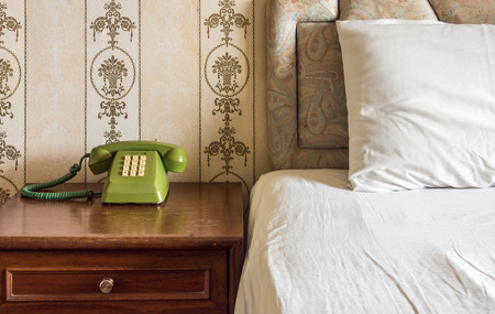 headboard: Vintage interior with old landline telephone, bed, pillow, headboard, wooden nightstand and wallpaper in bedroom Stock Photo