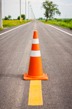 Orange traffic cone on center of country road. It is used for traffic warning and control.