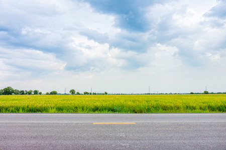 Natural landscape view of country road nearby paddy field in rural area of Thailand, Southeast Asia