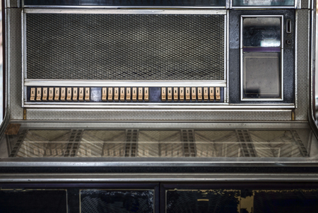 jukebox: Control panel of old classic coin-operated music box. It has a coin chute, playlists and buttons with numbers and letters on them for using a specific selection. Stock Photo
