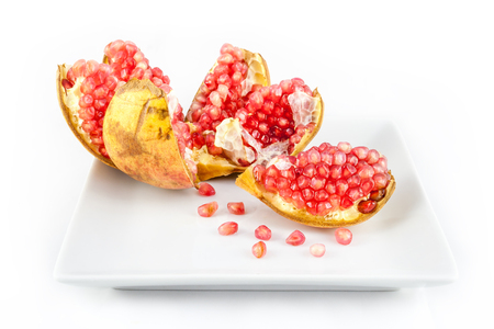 punica granatum: Opened ripe Pomegranate fruit in a plate. Punica granatum peeled to reveal clusters of fresh, juicy and gem-like seeds.