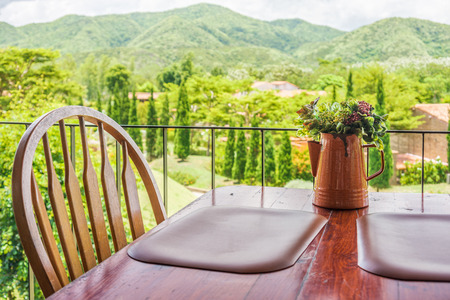 verandah: Vintage vase on wooden table and chair. The interior decoration on terrace with mountain range view. Stock Photo