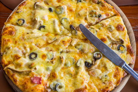 carnes y verduras: Round Pizza with knife on top. It is topped with meats, vegetables and cheese. Foto de archivo