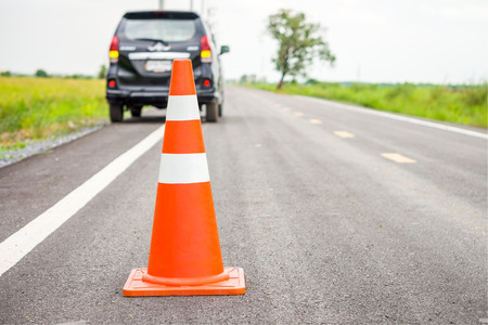 Orange traffic cone on country road. It is used for warning to broken down car on country road, Thailand.