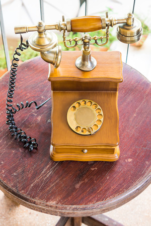 fixed line: Vintage landline telephone on wooden table. It is a rotary dial phone.