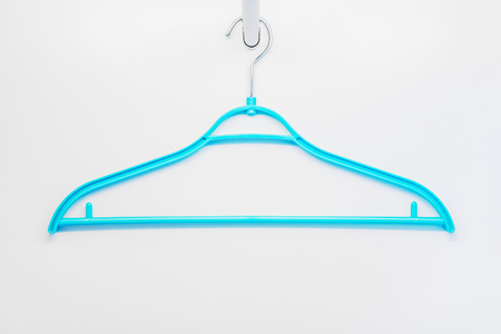 clotheshanger: Blue plastic clothes hanger. It is in a wardrobe. Stock Photo