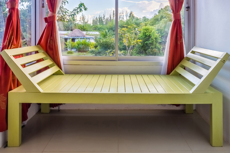 window bench: Modern green wooden bench nearby window. It is furniture for interior decoration.