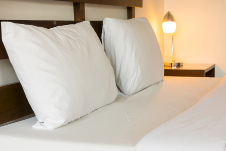 bedsheets: Double bed, pillows and bright lamp. The bed room is hotel room.