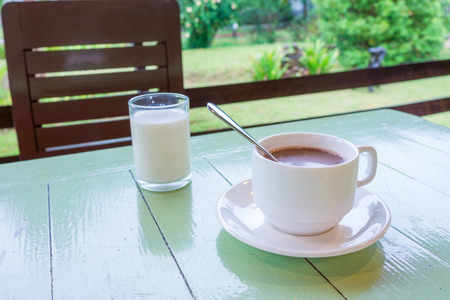 potation: Ceramic cup of coffee on wooden table. It is served with a glass of milk.