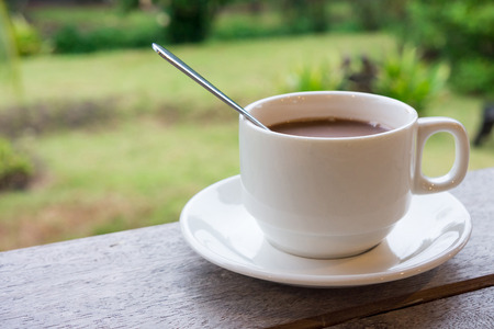 potation: Ceramic cup of coffee on table. It is a drink for refreshment.