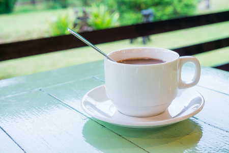 refreshment: Coffee break for refreshment. Ceramic cup of coffee on green wooden table. Stock Photo