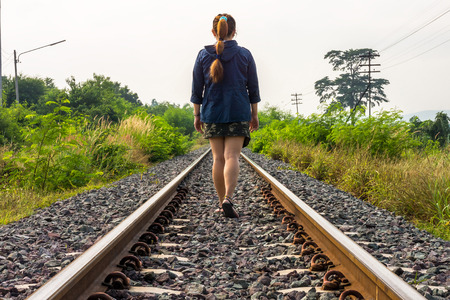Asian woman walking on railway track. The rail transport is the one most important transportation system in Thailand. Stock Photo