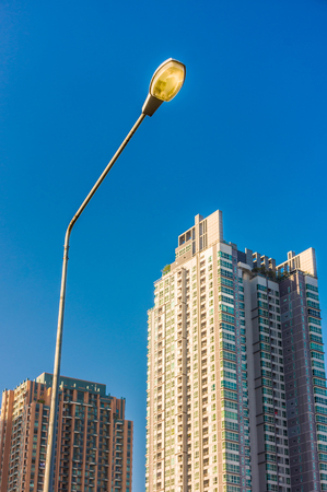 lighting system: Electrical streetlamp with high rise modern building background. The lighting system in Bangkok city, Thailand. Stock Photo