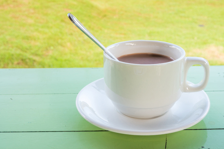 potation: Ceramic cup of coffee on table in backyard. It is a drink for refreshment.