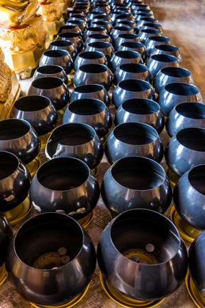 almsgiving: Row  of monks alms bowl. They are at Buddhist temple in Thailand.