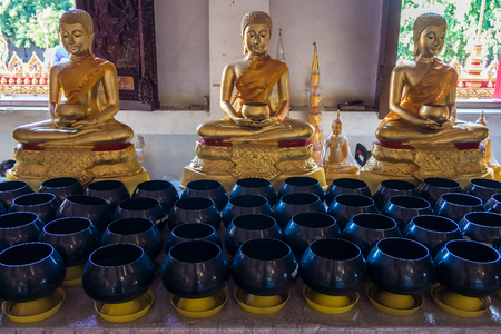 Buddha statues and row of monks alms bowl. They are at Buddhist temple in Thailand. Stock Photo