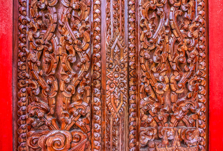 wood carving door: Thai wood carving art. The art on the door of Buddhist temple in Thailand.