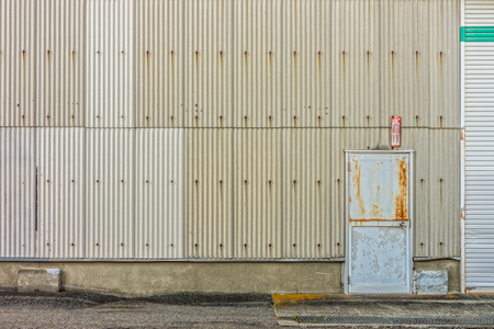 Steel door and corrugated wall of factory. Old rusty and grunge building.