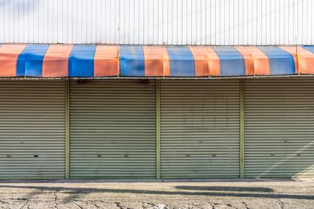 De gevel van de gesloten winkel. Er zijn luifel en het rollend stalen deuren van de winkel front.
