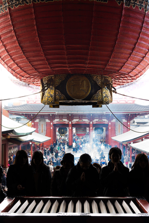 hondo: Silhouette of pilgrims and tourists praying in front of a saisen-bako or offertory box. They are in Hondo, the main hall of Senso-ji Temple.