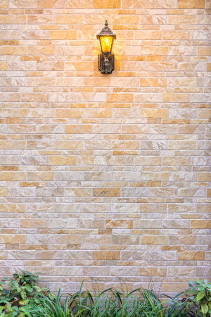 small garden: Exterior decoration of brick wall. The design consist of vintage hanging electrical lamp, natural brick block wall and small garden.
