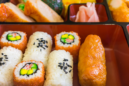 Food replicas of rolled cooked vinegary rice and sushi in Bento set. The model of Japanese delicacy.