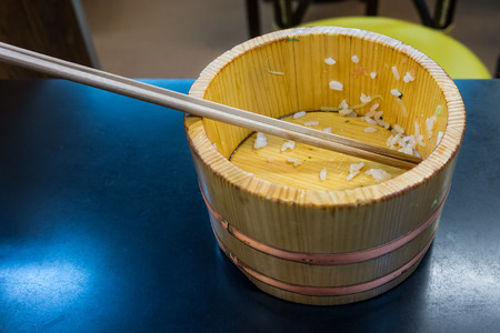 gobble: Empty vintage wooden bowl with chopsticks. The dish on a table in Japanese restaurant. Stock Photo