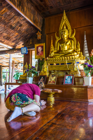 oneself: Asian woman pilgrim prostrating oneself in front of the Buddha statues in hall of  Wat Tham Khao Wong. Wat Tham Khao Wong is Thai Buddhist temple in Thailand,Asia. Stock Photo