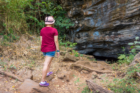 adventurer: Thai woman adventurer is walking to the Pu Wai cave. The cave is at Tham Khao Wong national park in Uthai Thani province, Thailand, Asia.