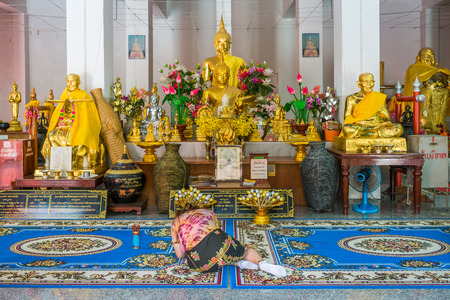 oneself: Asian woman pilgrim prostrating oneself in front of the Buddha statues in hall of Wat Pha Tung. Wat Pha Tung is Thai Buddhist temple in Ban Rai District, Thailand.
