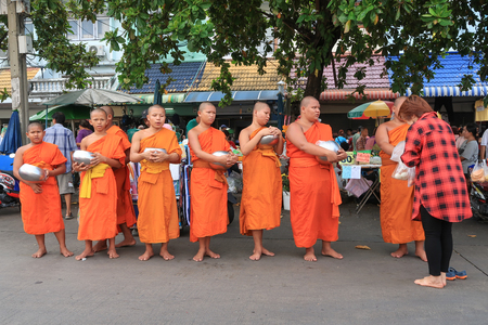 BANGKOK - JULY 19, 2016: Thai woman is offering her food to Buddhist novices at Asaha Puja Day or Sangha Day. Today is a Buddhist holy day and official holiday in Thailand. Editorial