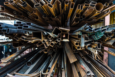 rustiness: Perspective of pile of construction metals in factory. They consist of square and rectangular steel tubes, iron pipes and bars.