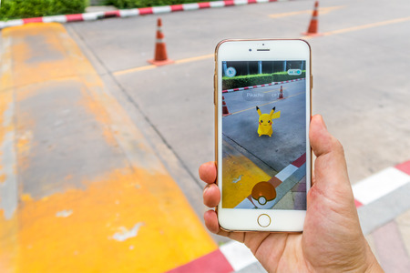 craze: Enthusiastic Pokemon player is catching Pikachu on street. The Pokemon Go has started craze in Thailand since August 6, 2016.
