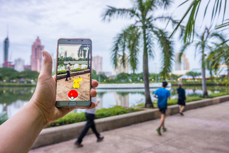 craze: BANGKOK - AUGUST 10, 2016: Enthusiastic Pokemon player is jogging and catching Pikachu in the street of Benchakiti Park. The Pokemon Go has started craze in Thailand since August 6, 2016.