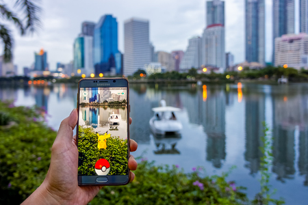 craze: BANGKOK - AUGUST 11, 2016: Enthusiastic Pokemon player is catching Pikachu at waterside in the Benchakiti Park. The Pokemon Go game has started craze in Thailand since August 6, 2016.