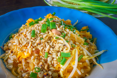 Plate of Thai fried noodles with eggs. It is served with raw fresh scallions. Stock Photo