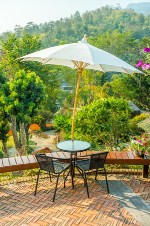 Modern round table and wicker chairs with sun shade umbrella. They are on a terrace or patio.
