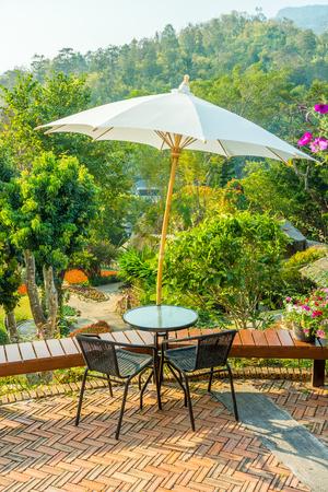 empedrado: Modernas de mesa y sillas con mimbre redondo sombrilla sombra. Ellos están en una terraza o un patio.