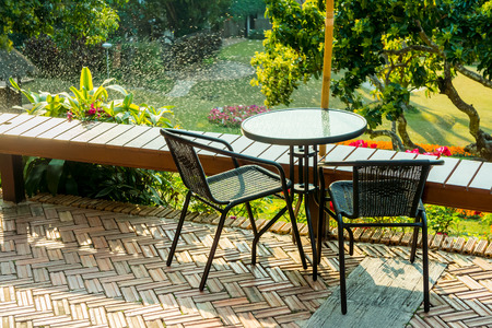 round chairs: Modern round table and wicker chairs with sunshine. They are on a terrace or patio.