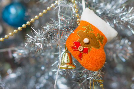 Hanging orange handicraft Xmas stocking and golden bell. The ornament and decoration on Christmas tree. Stock Photo