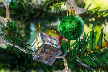 Green Xmas bauble on branch. Spherical decoration are used to festoon a Christmas tree. Stock Photo