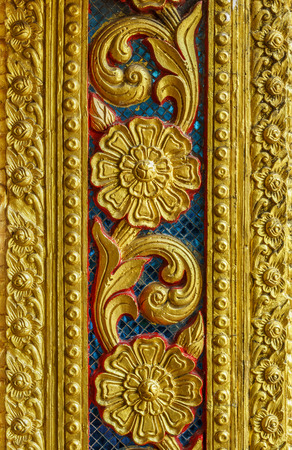 Vintage old golden floral sculpture on wall. The Thai design patterns are made from concrete and stucco.