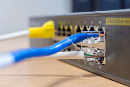 Closeup of LAN cable with RJ45 connector plugged into fast ethernet interface port of Switch. They are standard networking equipment. Stock Photo