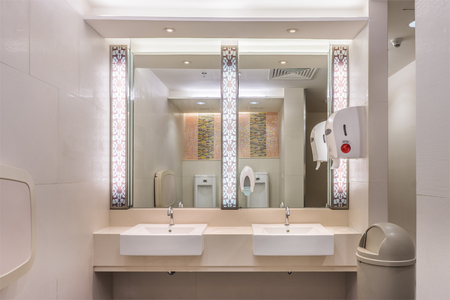 Clean modern restroom with light. It consists of new mirror, ceramic washbasins, granite countertop,liquid soap, plastic bin and toilet paper roll.