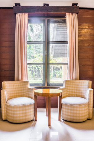 Classic twin fabric sofas and wooden round table. Interior design with window and curtains. Editorial
